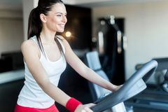 Beautiful, young lady riding the bicycle in a gym Royalty Free Stock Image