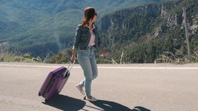 Beautiful young lady on rural road with suitcase hitchhiking on sunny day outdoors