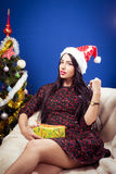 Beautiful young lady in Santa hat beside decorated Stock Photos