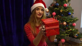 Beautiful young lady in santa hat having fun with christmas gift and smiling stock video