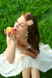 Beautiful young lady with sappy apple. Adorable happy young lady with beautiful sappy apple over green grass Stock Photo