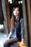 Beautiful young lady setting on the wooden door Stock Photography