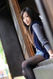 Beautiful young lady setting on the wooden door Stock Photo