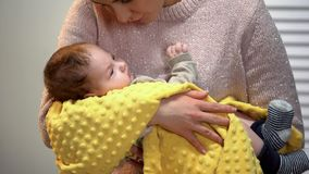 Beautiful young lady singing little baby to sleep, holding carefully in arms royalty free stock photography