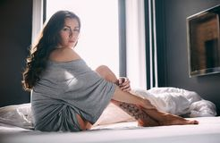 Beautiful young lady sitting on bed Royalty Free Stock Photos
