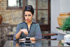 Beautiful young lady sitting in the cafe for a cup of coffee Royalty Free Stock Photos