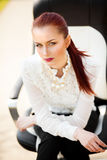 Beautiful young lady sitting on chair looking straight Royalty Free Stock Photography
