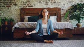 Beautiful young lady is sitting in lotus position on bedroom floor and enjoying meditation, harmony and peace. Modern stock footage
