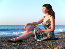 Beautiful Young Lady Sitting on Pebble. Beach on Sunrise Royalty Free Stock Photography