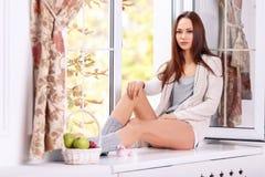 Beautiful young lady is sitting on the windowsill Stock Image