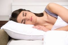 Beautiful young lady sleeping in bed. Stock Photo