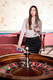 Beautiful young lady stay near roulette table Stock Images
