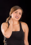 Beautiful young lady Suffer crick after workout in a black background Stock Photography