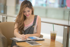 The Beautiful young lady with tablet sitting at the summer terra Stock Image
