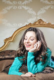 Beautiful young lady talking on mobile phone lying on bed happy smile. Closeup portrait Stock Photos