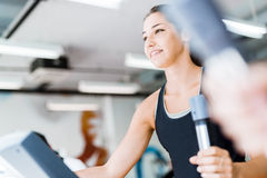Beautiful young lady using the elliptical trainer Royalty Free Stock Images