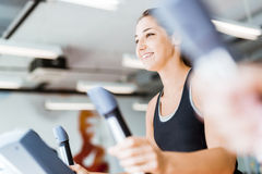 Beautiful young lady using the elliptical trainer Royalty Free Stock Photos