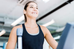 Beautiful young lady using the elliptical trainer Stock Photos