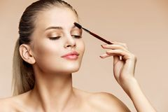 Beautiful young lady using eyebrow brush. Close up of woman finishing her makeup on beige background. Beauty Stock Photos