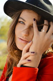 Beautiful young lady wearing hat and red coat in Stock Photos