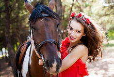 Beautiful young lady wearing red dress riding a horse at sunny summer day. Brunette with long curly hair with flowers on her head Stock Photography