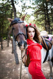 Beautiful young lady wearing red dress riding a horse at sunny summer day. Brunette with long curly hair with flowers on her head Royalty Free Stock Image