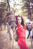 Beautiful young lady wearing red dress riding a horse at sunny summer day. Brunette with long curly hair with flowers on her head Royalty Free Stock Photography