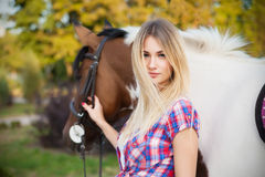 Beautiful young lady wearing t-shirt and jeans riding a horse at Royalty Free Stock Image