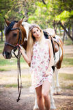 Beautiful young lady wearing vintage dress riding a horse at sun. Ny summer day. Blond long hair with and a happy smile. Perfect skin and makeup. Close up Royalty Free Stock Photo