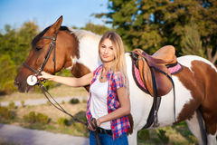 Beautiful young lady wearing vintage t-shirt and jeans riding a stock image