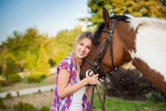Beautiful young lady wearing vintage t-shirt and jeans riding a Stock Images