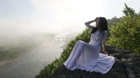 Beautiful young lady in a white wedding dress sitting alone near the river with her eyes closed Stock Images