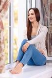Beautiful young lady on the windowsill Royalty Free Stock Photo