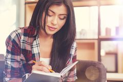 Beautiful young lady writing down ideas in notebook Royalty Free Stock Photo