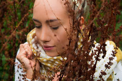Beautiful young latin girl behind some forest weeds. Close up shot of beautiful young latin girl behind some forest weeds Stock Photo