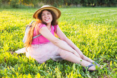 Beautiful young laughing naughty woman sitting outdoors and smiling.  Stock Image