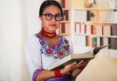 Beautiful young lawyer wearing traditional andean blouse and glasses, holding book reading, bookshelves background.  Stock Photography