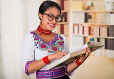 Beautiful young lawyer wearing traditional andean blouse and glasses, holding book reading, bookshelves background.  Stock Photo