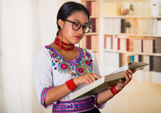 Beautiful young lawyer wearing traditional andean blouse and glasses, holding book reading, bookshelves background.  Royalty Free Stock Photography