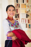 Beautiful young lawyer wearing traditional andean blouse, holding red jacket smiling to camera, bookshelves background Stock Photography