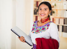Beautiful young lawyer wearing traditional andean blouse with necklace, holding laptop and red jacket smiling Stock Images