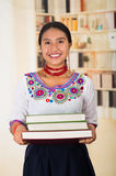 Beautiful young lawyer wearing traditional andean blouse and red necklace, holding stack of books, smiling to camera Royalty Free Stock Images