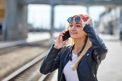 A girl talking on the phone raised her glasses to see something. Beautiful, young in a leather jacket a girl talking on the phone raised her glasses to see Royalty Free Stock Photo