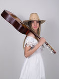 Beautiful young leggy blond Country girl in a litl white dress and cowboy hat with a guitar Royalty Free Stock Image