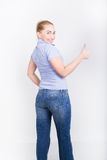 Beautiful young leggy blond girl in a jeans and a blue shirt  in a boots, full height posing, shows thumb Royalty Free Stock Images