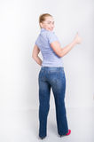 Beautiful young leggy blond girl in a jeans and a blue shirt  in a boots, full height posing, shows thumb Royalty Free Stock Photos