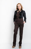 Beautiful young leggy blonde in a  brown top, black jacket and pants posing Royalty Free Stock Images
