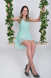 Beautiful young leggy blonde in a little green dress and gray high-heeled shoes on a swing, wooden swing suspended from Stock Photo