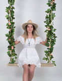 Beautiful young leggy blonde in a little white dress and white cowboy hat on a swing, wooden swing suspended from a rope Stock Photos