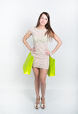 Beautiful young leggy brunette in a little gray cocktail dress full height. holding shopping bags, she goes shopping Royalty Free Stock Photo
